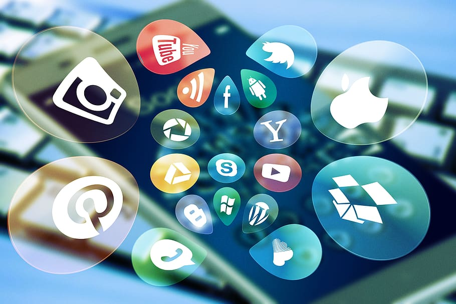 Icons of various social media platforms on an out-of-focus background with a cell phone and keyboard.